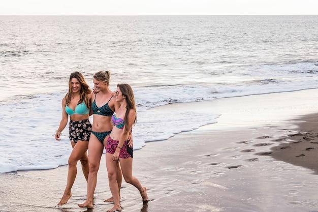 Три молодые красивые девушки-модели вместе гуляют по берегу