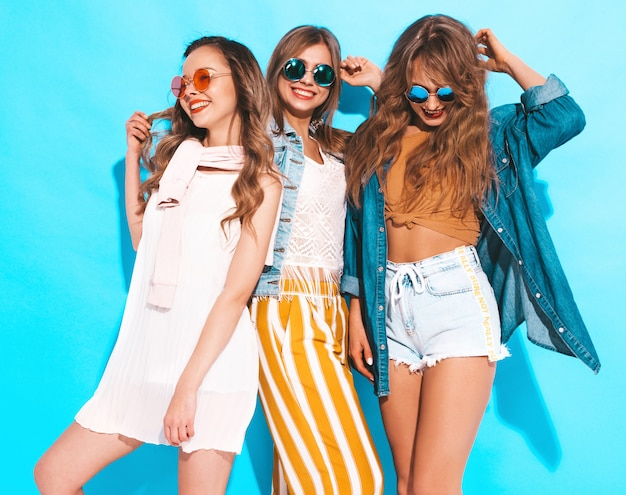 Three young beautiful smiling girls in trendy summer casual clothes. sexy carefree women posing. positive models in sunglasses