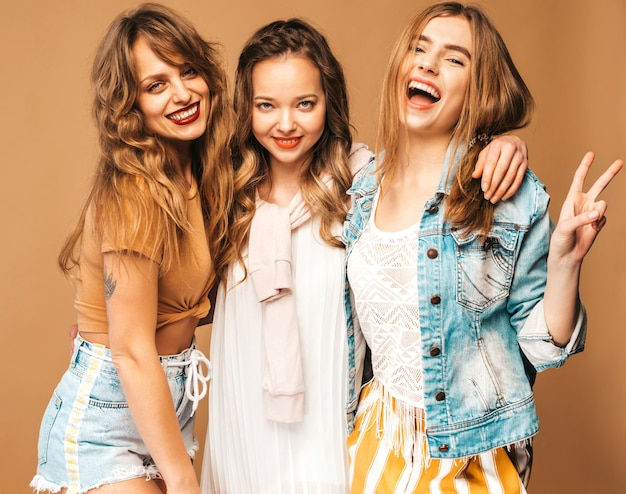 Three young beautiful smiling girls in trendy summer casual clothes. sexy carefree women posing. positive models