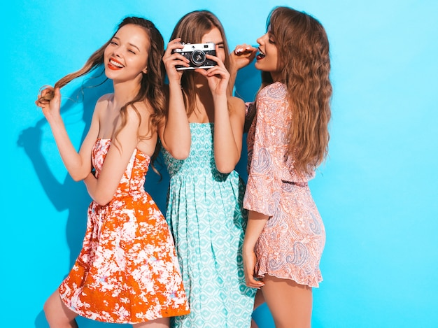 Three young beautiful smiling girls in trendy summer casual dresses. sexy carefree women posing. taking pictures on retro camera