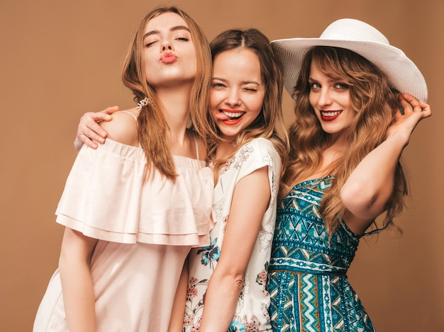 Three young beautiful smiling girls in trendy summer casual dresses. sexy carefree women posing.