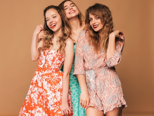 Three young beautiful smiling girls in trendy summer casual dresses and in sunglasses. sexy carefree women posing.