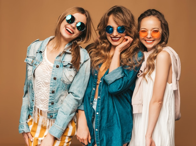 Three young beautiful smiling girls in trendy summer casual jeans clothes. sexy carefree women posing. positive models in sunglasses
