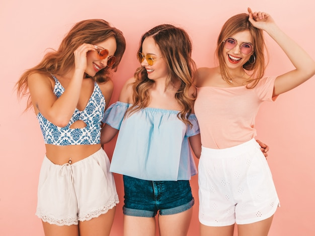 Three young beautiful smiling girls in trendy summer clothes. sexy carefree women posing. positive models having fun. hugging