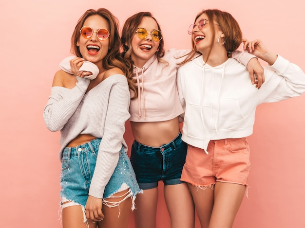 Three young beautiful smiling girls in trendy summer clothes. sexy carefree women posing. positive models having fun