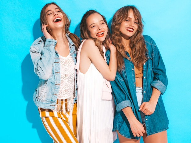 Three young beautiful smiling girls in trendy summer colorful clothes. sexy carefree women isolated on blue. positive models