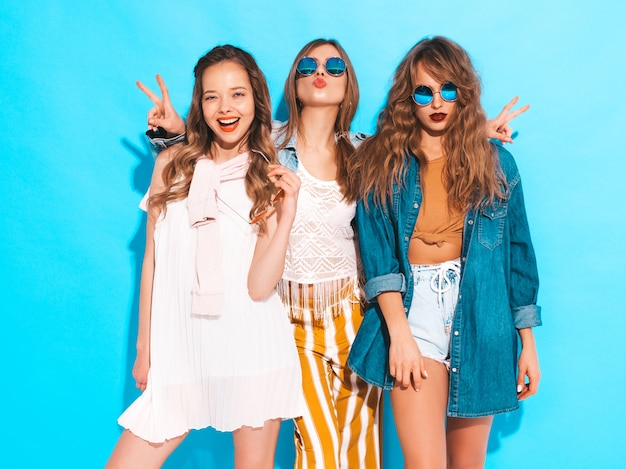 Three young beautiful smiling girls in trendy summer colorful clothes. sexy carefree women in sunglasses isolated on blue. positive models