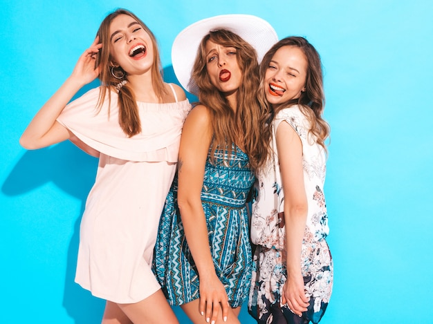 Three young beautiful smiling girls in trendy summer colorful dresses. sexy carefree women in. and making funny faces