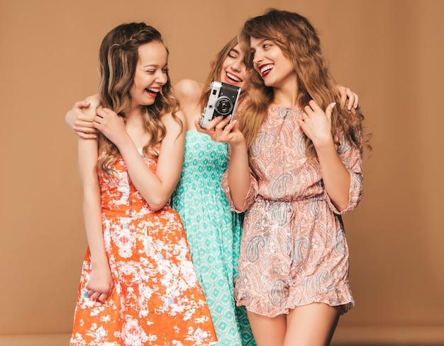 Tre giovani belle ragazze sorridenti in abiti colorati alla moda estate. posa sexy spensierata delle donne. scattare foto con fotocamera retrò