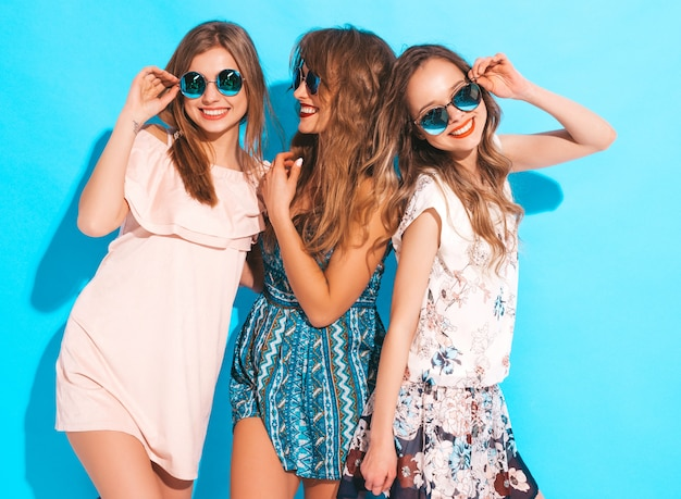 Three young beautiful smiling girls in trendy summer colorful dresses. sexy carefree women in sunglasses.