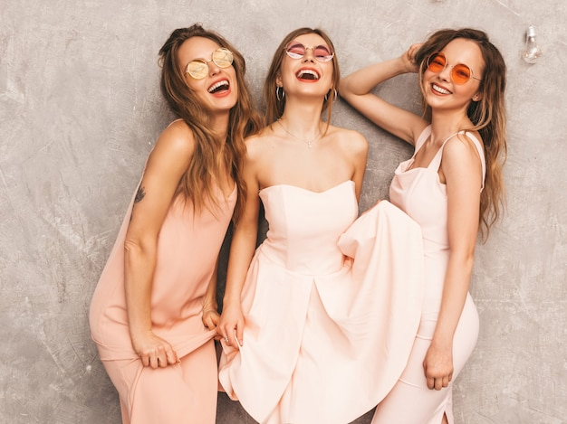 Three young beautiful smiling girls in trendy summer light pink dresses. sexy carefree women posing. positive models in round sunglasses having fun