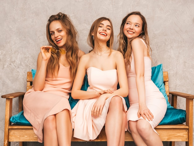Three young beautiful smiling girls in trendy summer pink dresses. sexy carefree women sitting on sofa in luxury interior. positive models having fun and communicating
