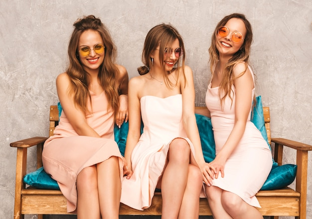 Three young beautiful smiling girls in trendy summer pink dresses. sexy carefree women sitting on sofa in luxury interior. positive models in round sunglasses having fun and communicating