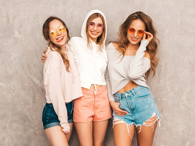 Three young beautiful smiling girls in trendy summer sport clothes. sexy carefree women posing. positive models in round sunglasses having fun. hugging