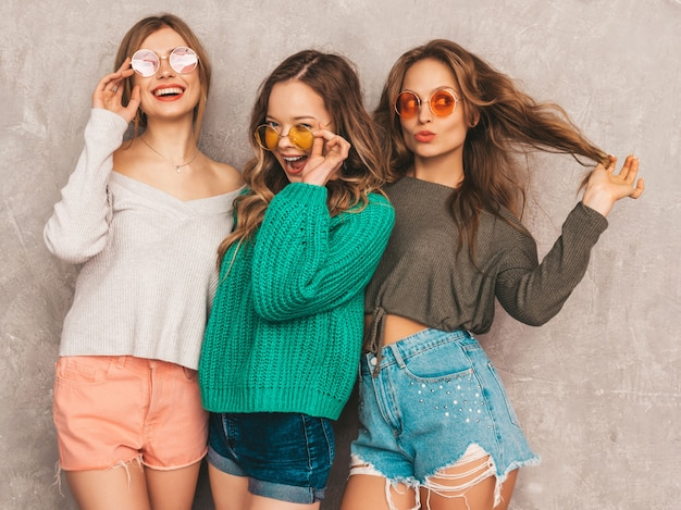 Three young beautiful smiling gorgeous girls in trendy summer clothes.  sexy carefree women posing. positive models having fun in round sunglasses
