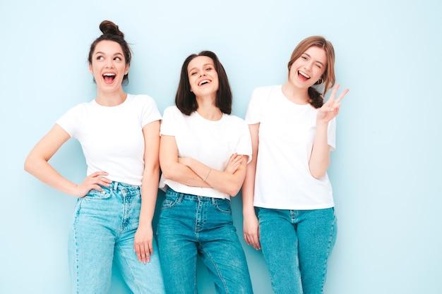 Три молодые красивые улыбающиеся хипстерские девушки в модной той же летней белой футболке и джинсовой одежде