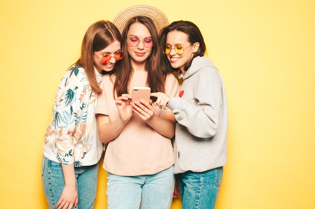 Three young beautiful smiling hipster female in trendy clothes