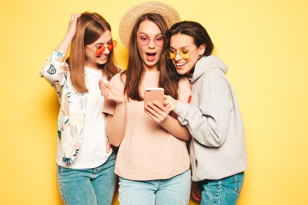 Three young beautiful smiling hipster female in trendy same summer clothes