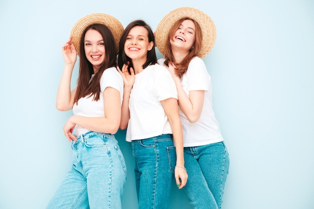 Three young beautiful smiling hipster female in trendy same summer white t-shirt and jeans clothes