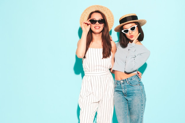 Three young beautiful smiling hipster female in trendy summer clothes