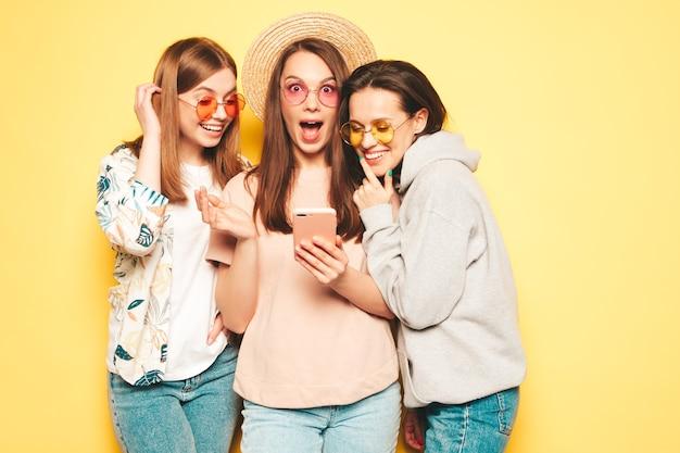 Tre giovani belle donne hipster sorridenti in t-shirt estiva alla moda e vestiti di jeans