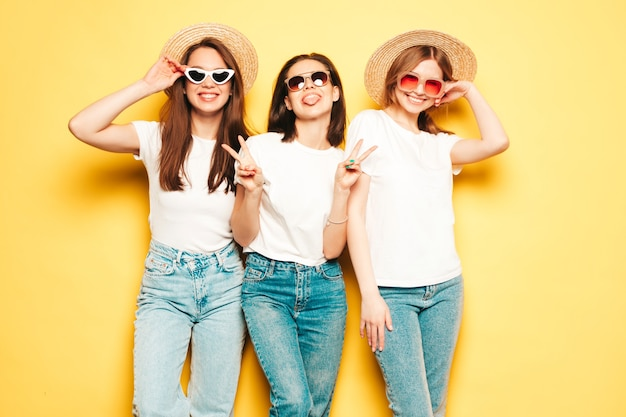 Three young beautiful smiling hipster female in trendy summer white t-shirt and jeans clothes