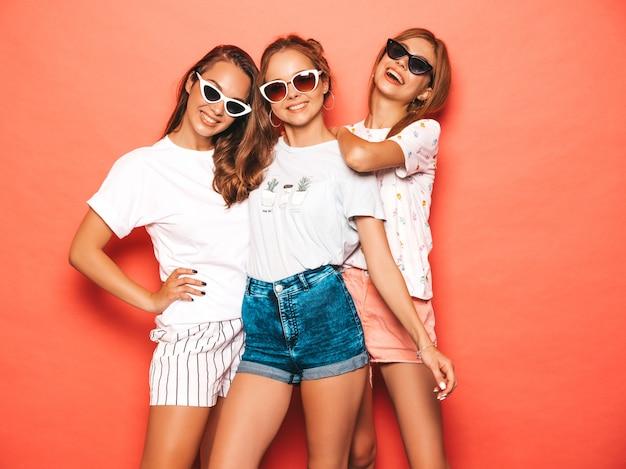 최신 유행의 여름 옷을 입고 세 젊은 아름 다운 웃는 hipster 여자. 분홍색 벽 근처 포즈 섹시 평온한 여성. 긍정적이고 재미있는 모델. 선글라스에