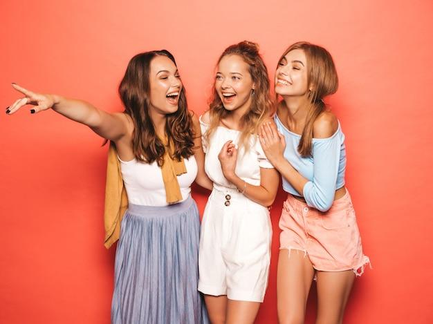 최신 유행의 여름 옷을 입고 세 젊은 아름 다운 웃는 hipster 여자. 분홍색 벽 근처 포즈 섹시 평온한 여성. 긍정적 인 모델 재미. 상점 판매를 가리키는