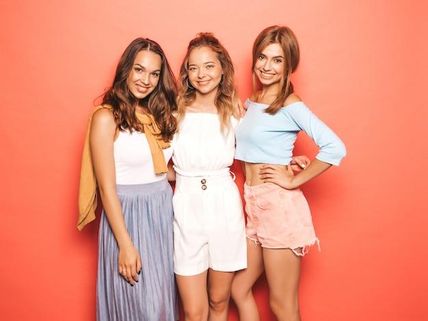 Три молодые красивые улыбающиеся битник девушки в модной летней одежде. сексуальные беззаботные женщины позируют возле розовой стены. веселые позитивные модели