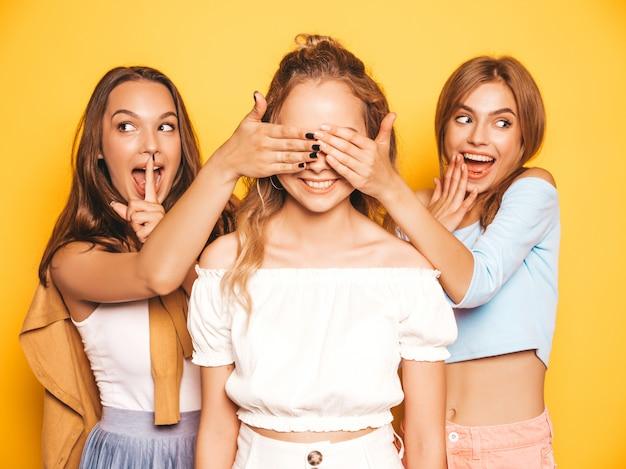 트렌디 한 여름 옷에 세 젊은 아름 다운 웃는 힙 스터 소녀. 노란색 벽 근처에 포즈 섹시 평온한 여성. 친구 놀라움 모델. 그들은 그녀의 눈을 덮고 뒤에서 포옹