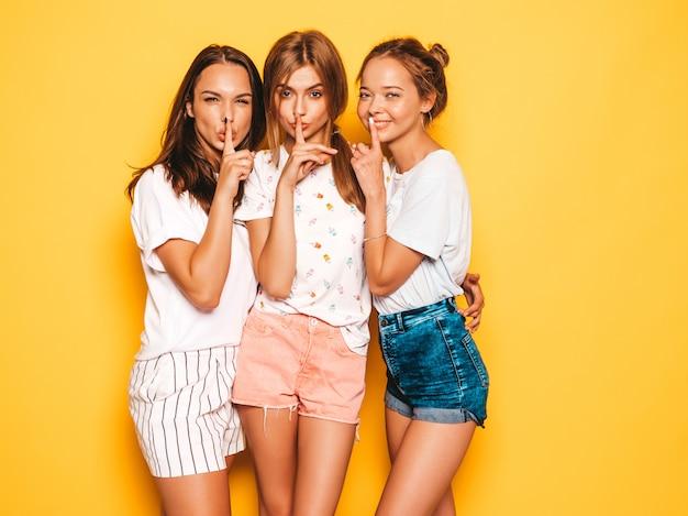 최신 유행의 여름 옷을 입고 세 젊은 아름 다운 웃는 hipster 여자. 노란 벽 근처 포즈 섹시 평온한 여성. 미쳐가는 긍정적 인 모델. 허쉬 손가락 침묵 기호, 제스처를 보여주는