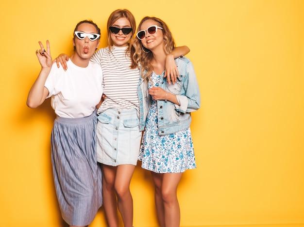 최신 유행의 여름 옷을 입고 세 젊은 아름 다운 웃는 hipster 여자. 노란 벽 근처 포즈 섹시 평온한 여자입니다. 선글라스로 재미있게 즐기는 긍정적 인 모델.