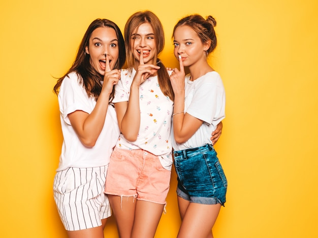 최신 유행의 여름 옷을 입고 세 젊은 아름 다운 웃는 hipster 여자. 노란 벽 근처 포즈 섹시 평온한 여자입니다. 자장 손가락 침묵 기호, 제스처를 보여주는 긍정적 인 모델
