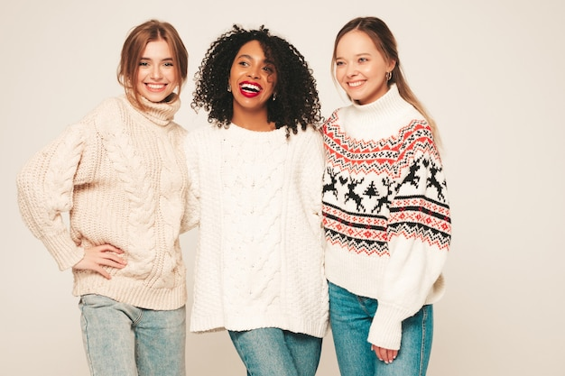 トレンディな冬のセーターを着た3人の若い美しい笑顔のヒップスターの女の子。楽しさと抱擁を持っているポジティブモデル