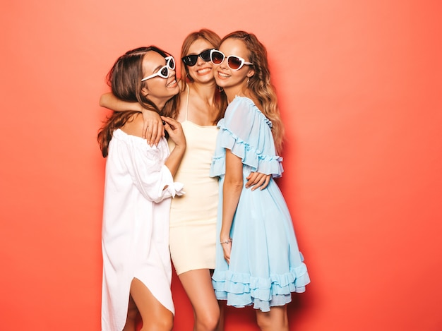 Three young beautiful smiling hipster girls in trendy summer clothes. sexy carefree women posing near pink wall. positive models going crazy and having fun. in sunglasses