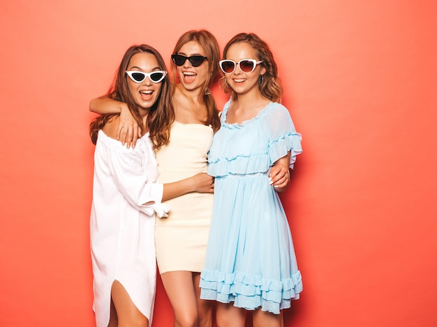 Three young beautiful smiling hipster girls in trendy summer clothes. sexy carefree women posing near pink wall. positive models going crazy and having fun in sunglasses