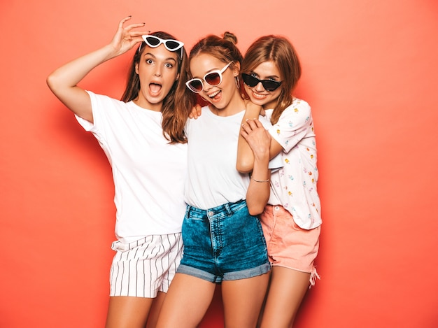 Three young beautiful smiling hipster girls in trendy summer clothes. sexy carefree women posing near pink wall. positive models going crazy and having fun
