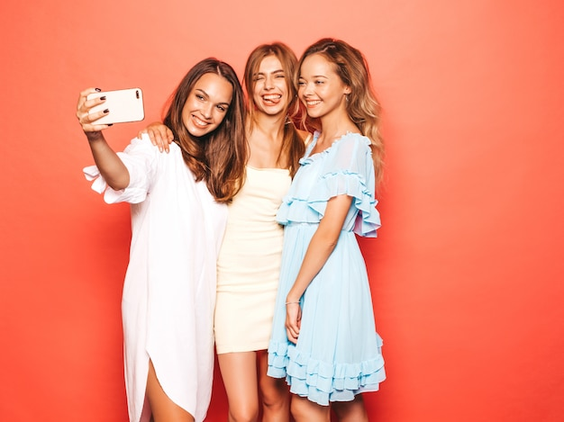Three young beautiful smiling hipster girls in trendy summer clothes. sexy carefree women posing near pink wall. positive models going crazy.taking selfie self portrait photos on smartphone