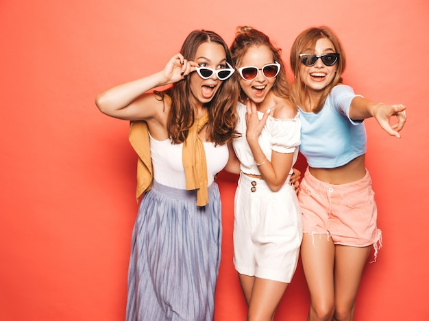 Three young beautiful smiling hipster girls in trendy summer clothes. sexy carefree women posing near pink wall. positive models having fun.pointing on shop sales