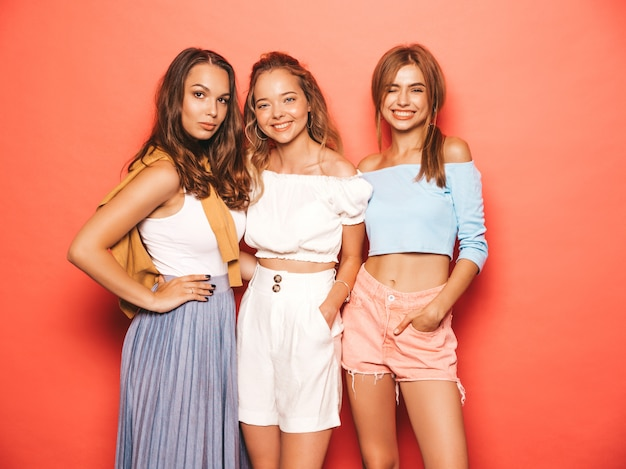 Three young beautiful smiling hipster girls in trendy summer clothes. sexy carefree women posing near pink wall. positive models having fun