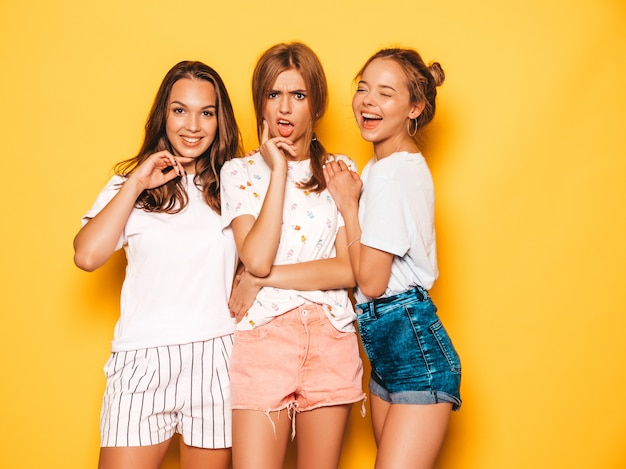 Three young beautiful smiling hipster girls in trendy summer clothes. sexy carefree women posing near yellow wall. positive models going crazy and having fun.hugging