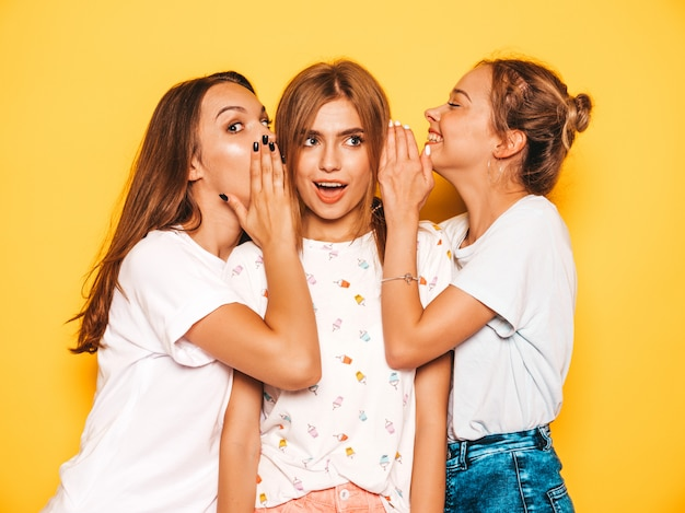 Three young beautiful smiling hipster girls in trendy summer clothes. sexy carefree women posing near yellow wall. positive models going crazy and having fun.share secrets, gossip