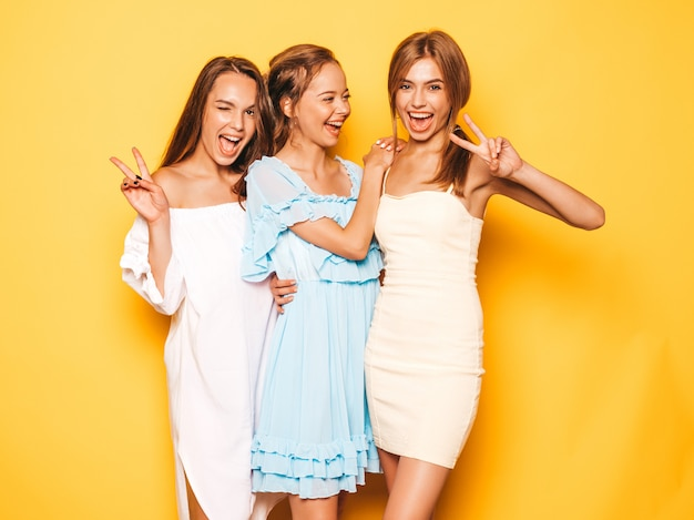 Three young beautiful smiling hipster girls in trendy summer clothes. sexy carefree women posing near yellow wall. positive models going crazy and having fun.shows peace sign