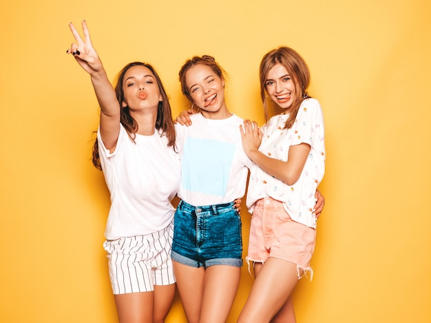 Three young beautiful smiling hipster girls in trendy summer clothes. sexy carefree women posing near yellow wall. positive models going crazy and having fun.they show tongue