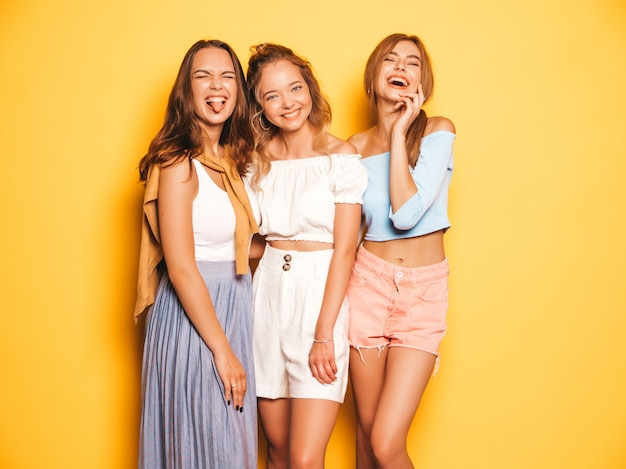 Three young beautiful smiling hipster girls in trendy summer clothes. sexy carefree women posing near yellow wall. positive models going crazy and having fun