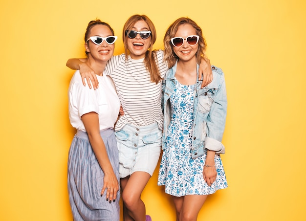 Three young beautiful smiling hipster girls in trendy summer clothes. sexy carefree women posing near yellow wall. positive models having fun. in sunglasses