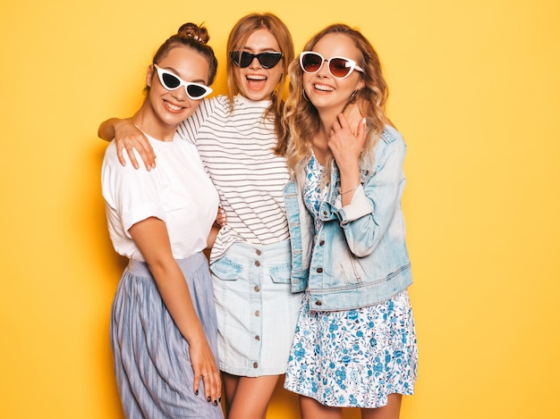 Three young beautiful smiling hipster girls in trendy summer clothes. sexy carefree women posing near yellow wall. positive models having fun