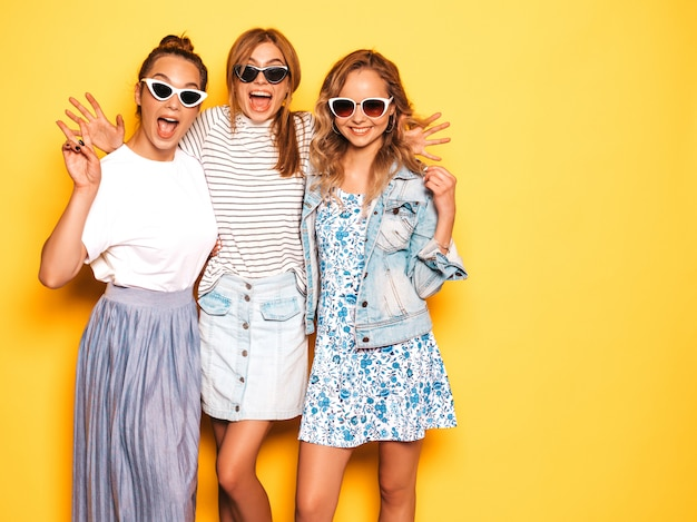 Three young beautiful smiling hipster girls in trendy summer clothes. sexy carefree women