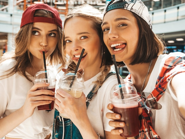 Three young beautiful smiling hipster girls in trendy summer clothes