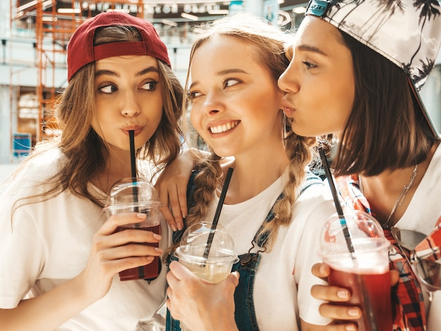 Three young beautiful smiling hipster girls in trendy summer clothes.